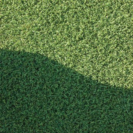 carpet and flooring: Artificial grass fake turf synthetic lawn field macro closeup with gentle shaded shadow area, green sports texture background with shade
