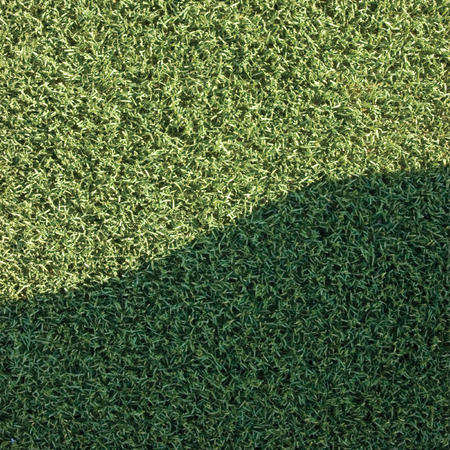 grass area: Artificial grass fake turf synthetic lawn field macro closeup with gentle shaded shadow area, green sports texture background with a shade
