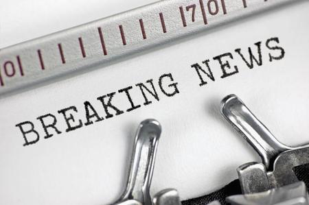 Macchina da scrivere modalità macro del primo piano di digitazione di testo Breaking News, grande dettaglio epoca stampa, tv, radio, internet mass media giornalismo metafora, giornali, riviste, trasmissioni giornalista televisivo ultime notizie lampo concetto girato in studio, orizzontale