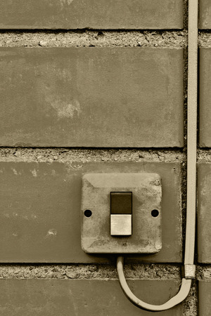 switch: Outdoor electric equipment control industrial button switch wire cable closeup, old aged weathered grungy brick wall background texture pattern, large detailed vertical textured grunge copy space in sepia Stock Photo