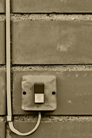 normal distribution: Outdoor electric equipment control industrial button switch wire cable closeup, old aged weathered grungy brick wall background texture pattern, large detailed vertical textured grunge copy space in sepia Stock Photo