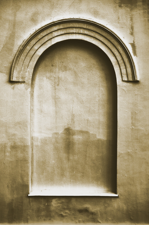 stucco texture: Old aged plastered faux arch false fake window stucco frame background copy space, dark vertical beige sepia texture Stock Photo