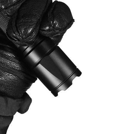 Gloved Hand Holding Tactical Flashlight, Bright Light Emiting Brightly Lit, Serrated Strike Bezel, Black Grain Leather Glove And Cop Jacket, Large Detailed Isolated Vertical Closeup, Patrolling Police Security Guard Staff Policeman, Covert Operations Patr Banco de Imagens