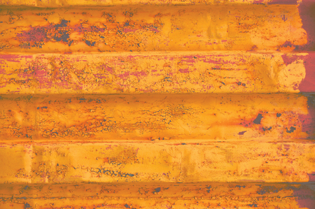 Yellow grunge sea freight container background, dark rusty corrugated pattern, red primer coating, horizontal rusted detailed steel texture, crakcked grungy metal paint detail, old aged weathered textured rust metallic copy space closeup