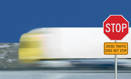 Red stop road sign, motion blurred truck vehicle traffic background, give way regulatory warning octagon, white octagonal frame, yellow cross traffic does not stop text signage, metallic pole post, blue summer sky Banque d'images