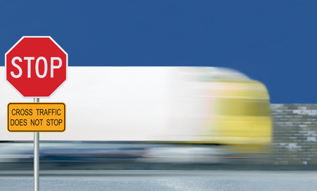 Red stop road sign, motion blurred truck vehicle traffic background, give way regulatory warning octagon, white octagonal frame, yellow cross traffic does not stop text signage, metallic pole post, blue summer sky Stock Photo