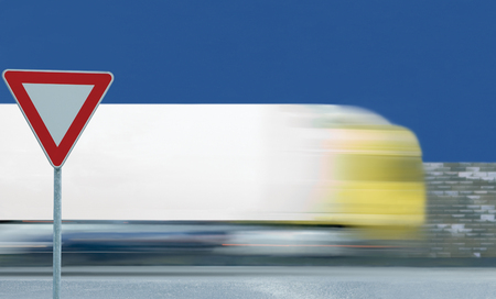 Give way yield road sign, motion blurred truck vehicle traffic background, white signage triangle red frame regulatory warning, metallic pole post, blue summer sky