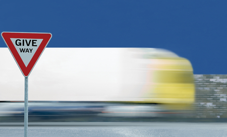 Give way text yield road sign, motion blurred truck vehicle traffic background, white signage triangle red frame regulatory warning, metallic pole post, blue summer sky
