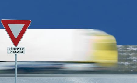 Nachgeben Ertrag Französisch céde le Passage Straßenschild, Bewegung verschwommen LKW Fahrzeug Verkehrshintergrund, weiße Beschilderung Dreieck roter Rahmen behördliche Warnung, metallischer Mastpfosten, blauer Sommerhimmel, Panneau Signalisierung cédez-le-Passage, Frankreich