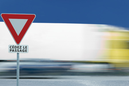 Give way yield french cédez le passage road sign, motion blurred truck vehicle traffic background, white signage triangle red frame regulatory warning, metallic pole post, blue summer sky, panneau signalisation cédez-le-passage, France