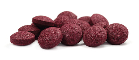 Black chokeberry fruit pills, large detailed isolated tablets macro closeup, organic raw aronia melanocarpa berry fruits pill pile, burgundy colored organic tablet heap, anthocyanins dietary supplement source berries Stock Photo