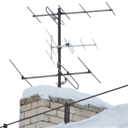 TV and communication aerials on snowy roof of residential house, multiple isolated dvb-t antennas winter scene, large detailed vertical closeup, rusty grunge vintage set Reklamní fotografie