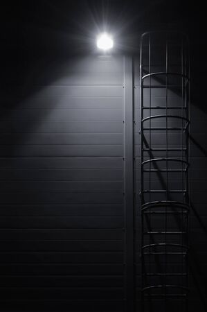 Fire emergency rescue access escape ladder stairway, roof maintenance stairs at night, bright shining lantern lamp light illumination glow shadows, rustic textured industrial building wall panels texture pattern, large detailed vertical closeup, copy space background, dark grey black key deserted scene Stockfoto