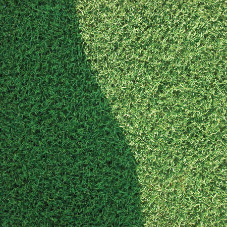 Artificial grass fake turf synthetic lawn field macro closeup, gentle shaded shadow area, green sports astroturf texture, vertical textured background pattern, large detailed shade