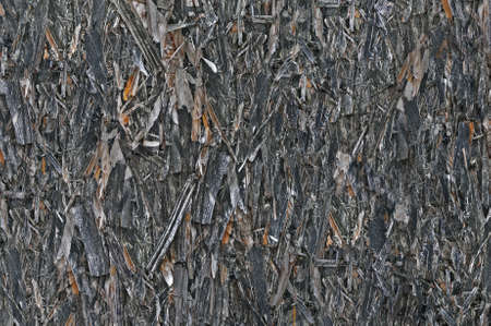 Old aged weathered oriented strand board OSB chipboard texture, grungy grey vertical pattern, horizontal rustic macro closeup, large detailed dark textured grunge ruined wooden background copy space, black, taupe, tan, brown, yellow beige detail Imagens