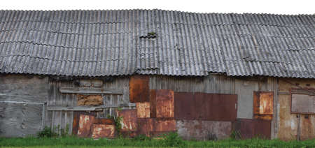 Old aged weathered wooden shack, grey plated wood boarding hut wall, patched planks, rusted metal plates Archivio Fotografico