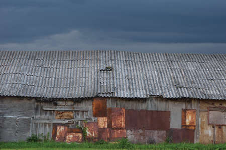 Old aged weathered wooden shack, grey plated wood boarding hut wall