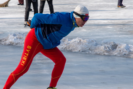 Shenyang, China; January 2018: Chinese skater on the icy lake have a healthy leisure skating in Shenyang open city park. Good equipment, glasses, gloves and hat. Éditoriale