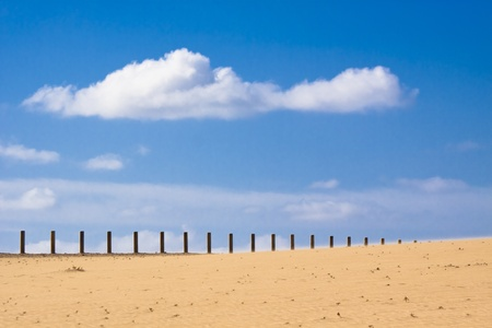 Wooden fence dissapearing into the infinity of the dessert. photo
