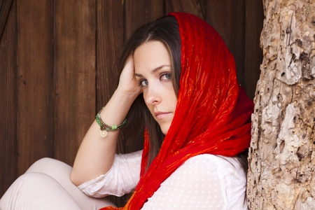 women face stare: Young attractive woman portraited siting infront of the wooden doors.