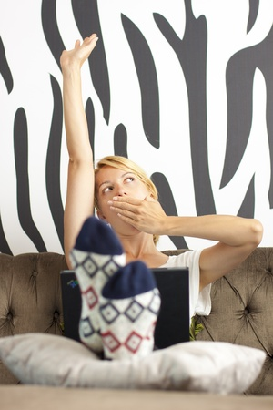 Beautiful young lady using laptop, stretching and yawning Stock Photo - 9711050
