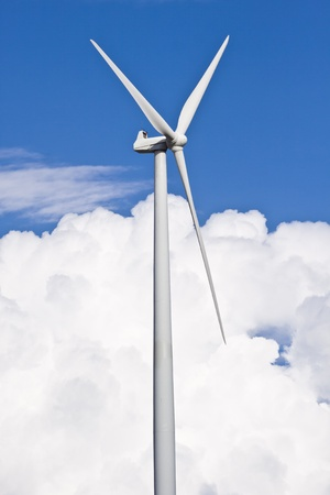 Wind turbine generating electricity with a nice white cloud on the sky photo