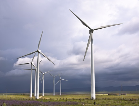 wind farm: Wind turbines generating electricity in a stormy weather. Stock Photo