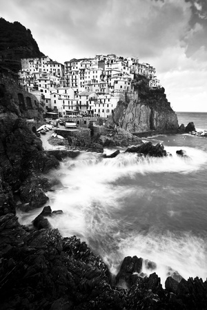 Manarola fisherman village in a dramatic windy weather in black and white. Manarola is one of five famous colorful villages of Cinque Terre (Nationa park) in Italy, suspended between sea and land on sheer cliffs upon the wild waves. photo