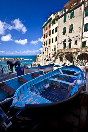 Fisherman village  Riomaggiore is one of five famous colorful villages of Cinque Terre in Italy, suspended between sea and land on sheer cliffs upon the  turquoise sea