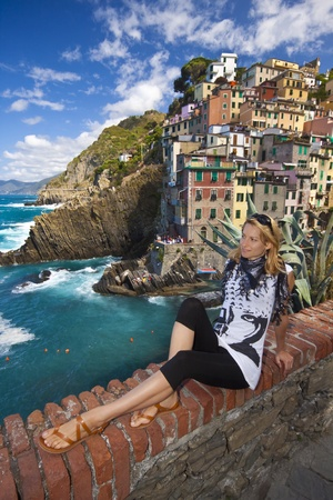 Young lady enjoying the beautiful scenery of Riomaggiore, one of five famous colorful villages of Cinque Terre in Italy, suspended between sea and land on sheer cliffs upon the  turquoise sea. photo