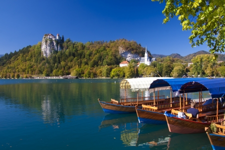 Traditional wooden boats on lake Bled, with the rocktop castle in the background  Slovenia