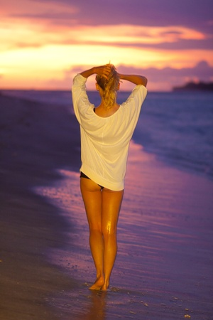 Attractive lady on the sandy tropical beach in saunset photo