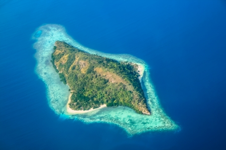Aerial view of uninhabited tropical island surrounded by a coral reef