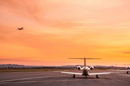 arrive: Airplane taking off at sunset  Stock Photo