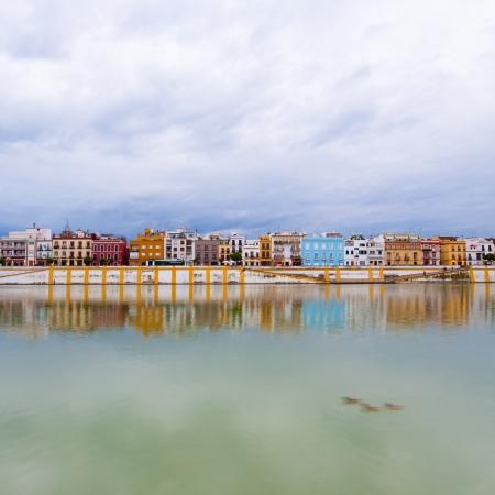 colores pastel: Colorido panorama de Sevilla ribere�a el d�a nublado, formando sorprendentes colores pastel y reflejos en el r�o. Foto de archivo