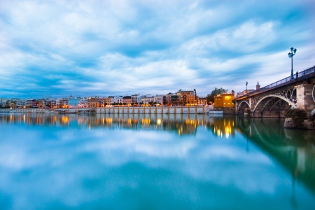 Dramatic panorama of Seville riverside at down and the Triana Bridge, the oldest bridge of Seville.