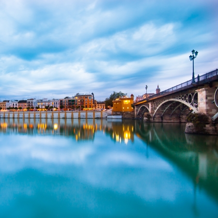 nightfall: Dramatic panorama of Seville riverside at down and the Triana Bridge, the oldest bridge of Seville.
