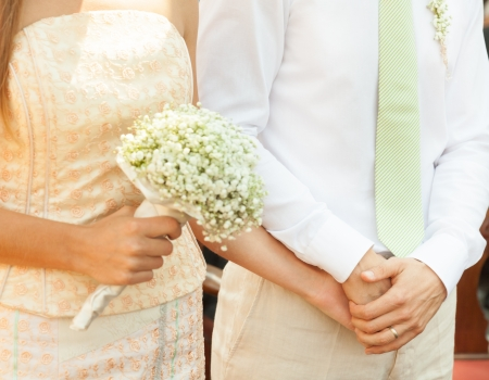 Close up of a bride and groom holding hands during wedding ceremony. photo