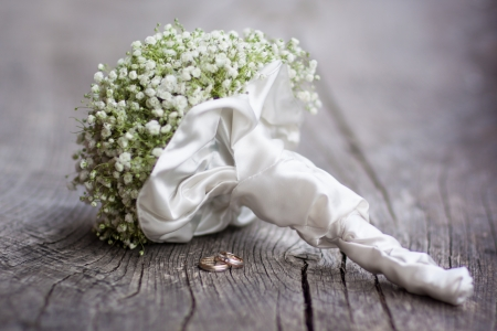 wedding symbol: Wedding  bouquet and rings on a dark wooden background.