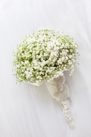 Wedding bouquet on a white vail. photo