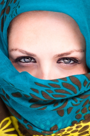 Beautiful Arab woman wearing blue scarf, stylish female close up face portrait, serious expression, stunning sensual beauty. Stock Photo - 15978156