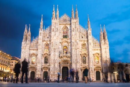 Milan Cathedral  Duomo di Milano  is the gothic cathedral church of Milan, Italy  Shot in the dusk from the square ful of people  photo