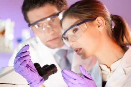 research study: Attractive young scientist and her post doctoral supervisor looking at the microscope slide in the forensic laboratory.