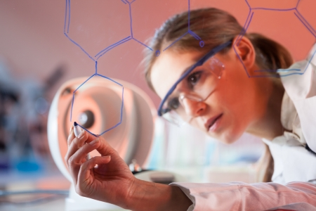 Portrait of a confident female health care professional in his working environment writing structural chemical formula on a glass board. Stock Photo - 16854979