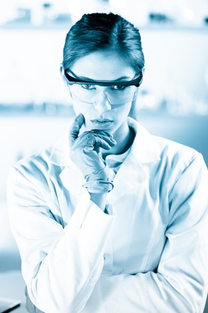 dental research: Portrait of an attractive, young, confident female health care professional in his working environment. Black and white, blue toned portrait.