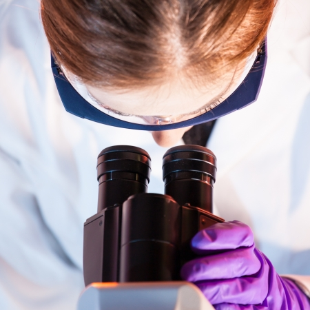 eyepiece: Scientist looking trough the microscope. Stock Photo
