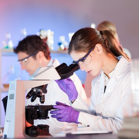 microscope slide: Attractive young researcher looking at the microscope slide in the life science laboratory.