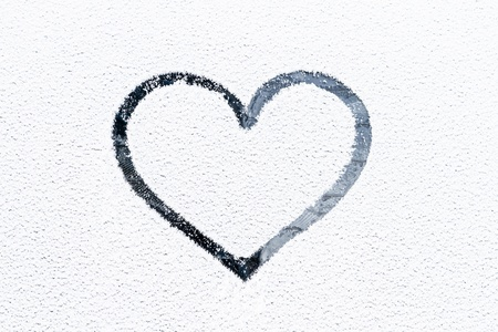 Heart drawn on a glass covered with fresh Christmas snow. Stock Photo