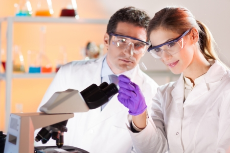 Attractive young scientist and her suprvisor looking at the microscope slide in the forensic laboratory. Stock Photo - 17083532