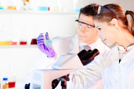 Chemical laboratory scene: attractive young student and her post doctoral supervisor scientist observing the green indicator solution color shift in glass flask. Stock Photo - 17083529